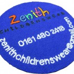 Round badge in blue with Zenith Childrenswear and phone number and email address on the front